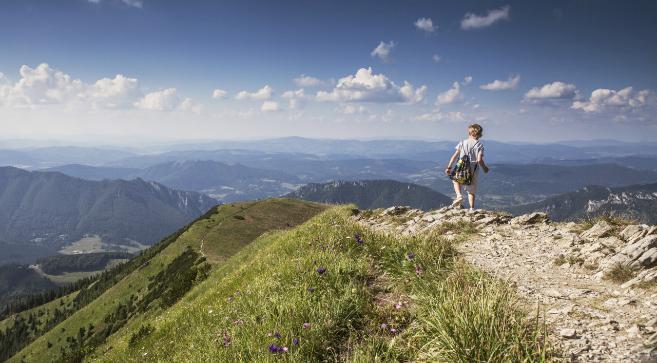 Boy with backpack on mountain hill foot path